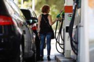 Un mujer reposta combustible en una gasolinera de Madrid