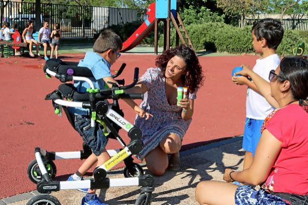 Niño discapacitado juega apartado del grupo.
