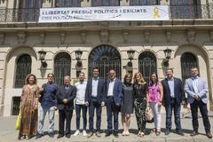 El alcalde de Lleida, Miquel Pueyo, junto a diversos regidores del gobierno municipal posan junto a la pancarta de apoyo a los presos políticos.
