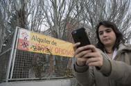 Una joven sujeta un móvil por la calle.