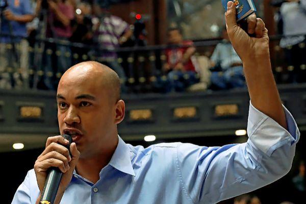 El diputado Hector Rodríguez levanta un tomo de la Constitución en la Asamblea Nacional en Caracas.