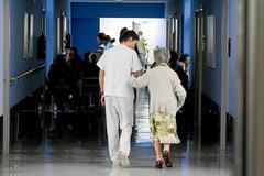 Una sanitaria acompaña a una anciana en una residencia.