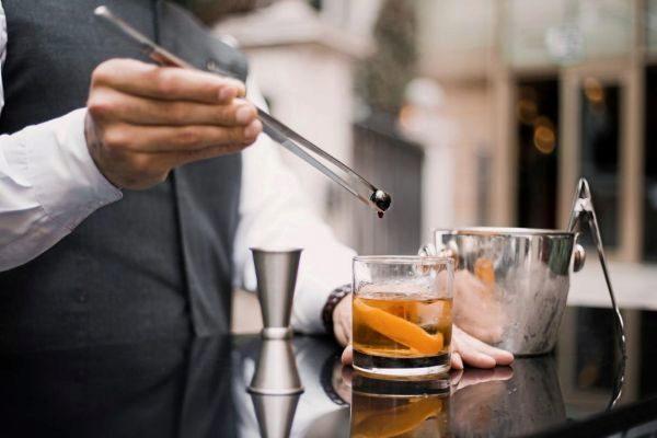 Un barman preparando un combinado.
