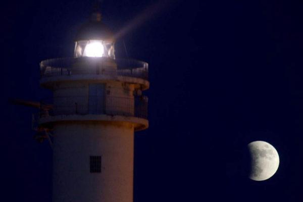 Eclipse lunar visto desde el Faro del Barrio del Charco, en el Puerto del Rosario, en Fuerteventura