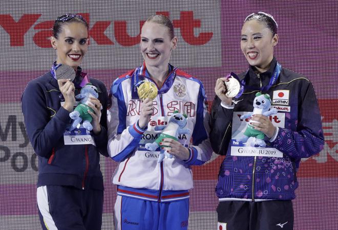 El podio tras la final artística de natación en solitario en el Mundial de Corea del Sur: en el centro, la medallista de oro Svetlana Romashina, de Rusia; a su dcha., Ona Carbonell con su medalla de plata, y a la izq., la medallista de bronce, Yukiko Inui, de Japón.