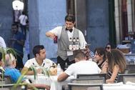 Un camarero atiende a unos clientes en la Plaza Mayor de Madrid.