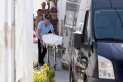 Un operario de la funeraria traslada uno de los cadáveres hallados ayer en Cortes de la Frontera.