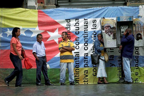Ciudadanos haciendo cola para usar un teléfono público, en Caracas.