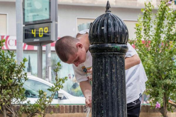 Un joven se refresca en una fuente de Murcia.