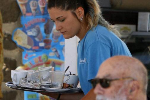 Una camarera atienda una terraza de un local en Benicàssim.