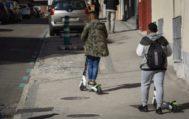 Dos jóvenes montan en patinete por la acera.