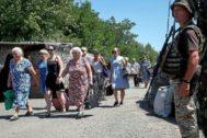 Un grupo de civiles cruza la línea del frente entre prorrusos y militares ucranianos, en Mayorsk.