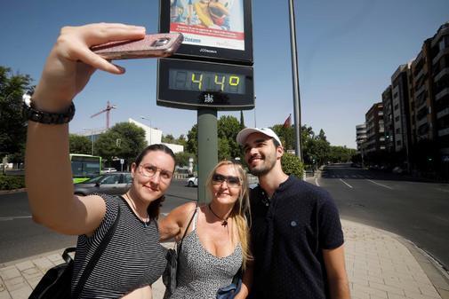 Unos turistas se fotografían ante un termómetro en el centro de...