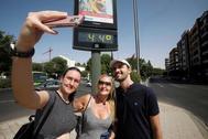 Unos turistas se fotografían ante un termómetro en el centro de Córdoba, en 'alerta naranja'.