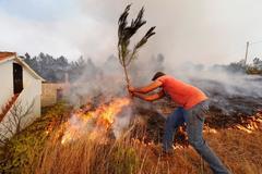 Un hombre trata de apagar las llamas en el pueblo de Colos (Portugal).