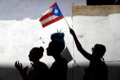 A woman waves a <HIT>Puerto</HIT> Rican flag during ongoing protests calling for the resignation of Governor Ricardo Rossello in San Juan
