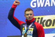 Adam Peaty celebra su medalla de oro en el podio.