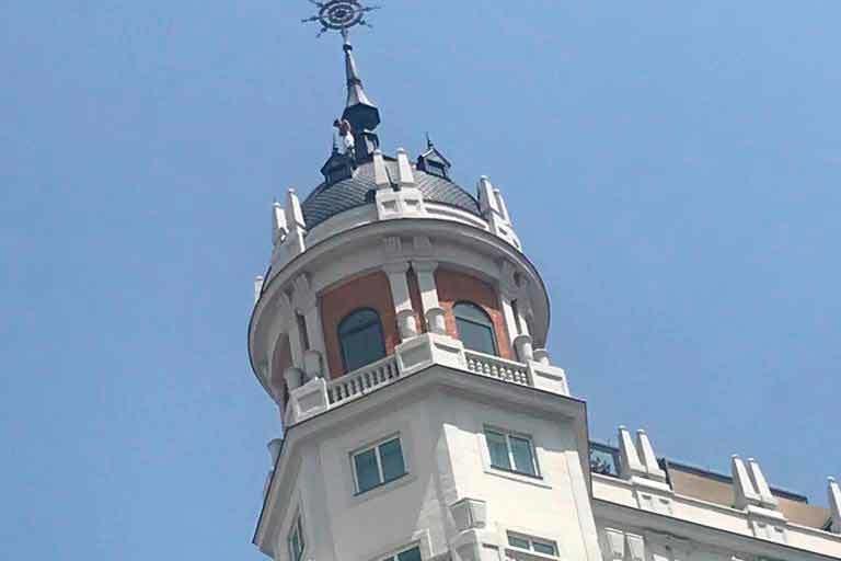 El hombre, en lo alto de una de las cúpulas de Gran Vía.