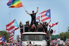 El cantante Ricky Martin, junto con otras personalidades puertorriqueñas, ondea una bandera en la manifestación de ayer, en San Juan, Puerto Rico.