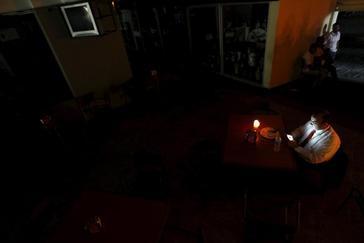 Un hombre en su casa de Caracas iluminadaúnicamente con una vela.