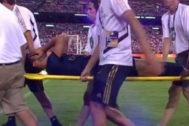Marco Asensio, retirado del campo entre gestos de dolor.