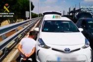 Uno de los detenidos junto al taxi donde transportaba la droga.