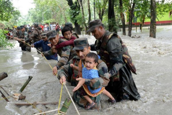 Nalbari (India).- Indian army soldiers help people to cross a flooded...