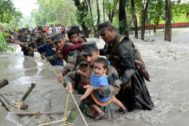 Nalbari (India).- Indian army soldiers help people to cross a flooded area at Dhamdhama in Nalbari diict of Assam, India, 24 July 2019. Indian army has been involved in the relief and rescue operation in different flood-affected villages in Assam. According to media reports, about 3 million people have been affected by floods across the state. (Inundaciones) EPA/