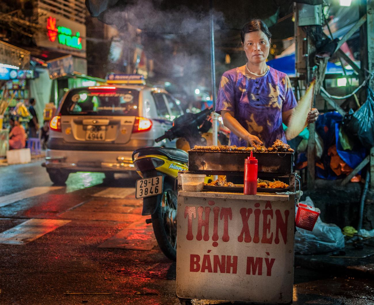 La cocina vietnamita tiene muchas cualidades y pocos defectos: es sabrosa y ligera, sumamente económica y muy  variada (más de 500 platos). En la imagen, mujer vendiendo pinchos de pollo a la brasa en Hanoi. Tras varias horas con su puesto en un concurrido cruce, lo que no venda estará listo para el día siguiente.