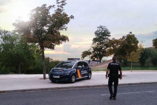 Un policía nacional se dirige a su coche patrulla.
