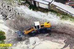 Una máquina excavadora intenta limpiar la carretera del Tour.