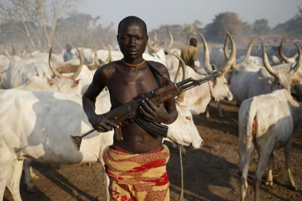 A man from <HIT>Dinka</HIT> tribe holds his AK 47 rifle in front of...
