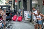 Un turista arrastra sus maletas en una calle del centro de Valencia.