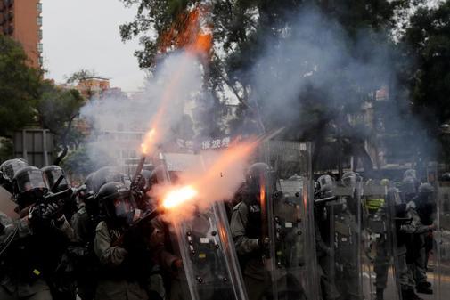 Policías lanzan gas lacrimógeno contra manifestantes durante una...