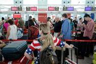 Los pasajeros hacen cola frente a los mostradores de facturación de la aerolínea española Iberia en el aeropuerto de El Prat de Barcelona.