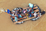 Migrantes guatemaltecos usan una balsa improvisada para cruzar el río Suchiate, desde Tecun Uman (Guatemala) a Ciudad Hidalgo (México).