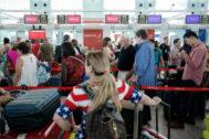 Pasajeros  hacen cola en los mostradores de Iberia en el aeropuerto de El Prat.