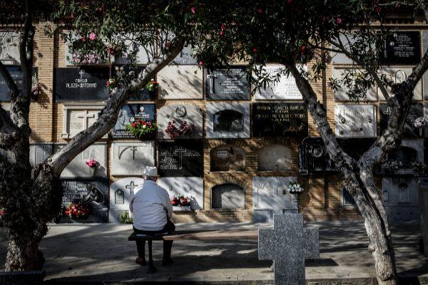 Una persona descansa en el banco de un cementerio de la Comunidad Valenciana.
