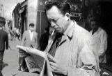Albert Camus leyendo un periódico en una calle deParís en 1959.