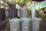 Empleados de la central manipulan varios contenedores.