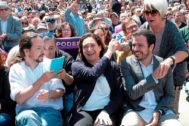 La alcaldesa de Barcelona, Ada Colau, entre Pablo Iglesias y Alberto Garzón en un acto del partido.