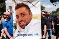 Varias personas llevan un cartel con la cara del caribnero asesinado durante su funeral.