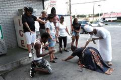 Miembros de un colectivo antiviolencia de Baltimore participan en un ritual en una gasolinera donde fue asesinado un adolescente de 17 años.