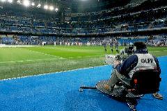 Una cámara de televisión graba un calentamiento en el Bernabéu.