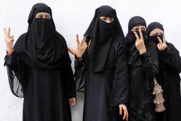 Varias mujeres musulmanas hacen el signo de la victoria en Nueva Delhi