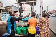 Un médico especializado en ébola registra la temperatura corporal de un joven en Goma.