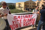"""Dos personas sostienen una pancarta que dice """"Salvar vidas no es crimen"""", en Agrigento (Italia)."""