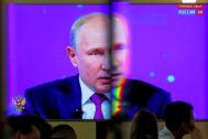 El presidente ruso, Vladimir Putin, aparece en una pantalla de una sala de prensa, en Moscú.