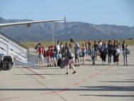 Pasajeros bajan de un avión estacionado en la pista del aeropuerto