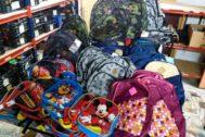En las imágenes, las mochilas recogidas y voluntarias preparando todo el material que reciben en la sede de la fundación.